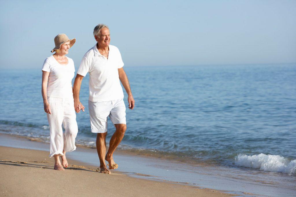 retired-couple-walking-on-beach