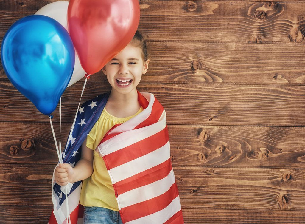 happy-girl-holding-red-white-and-blue-balloons-and-wrapped-in-an-american-flag-for-the-fourth-of-july