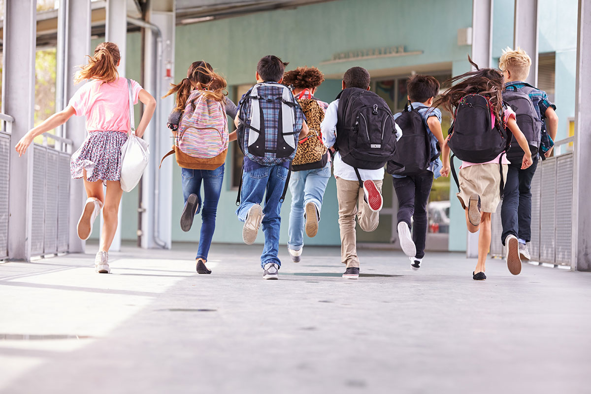 school children with large backpacks running