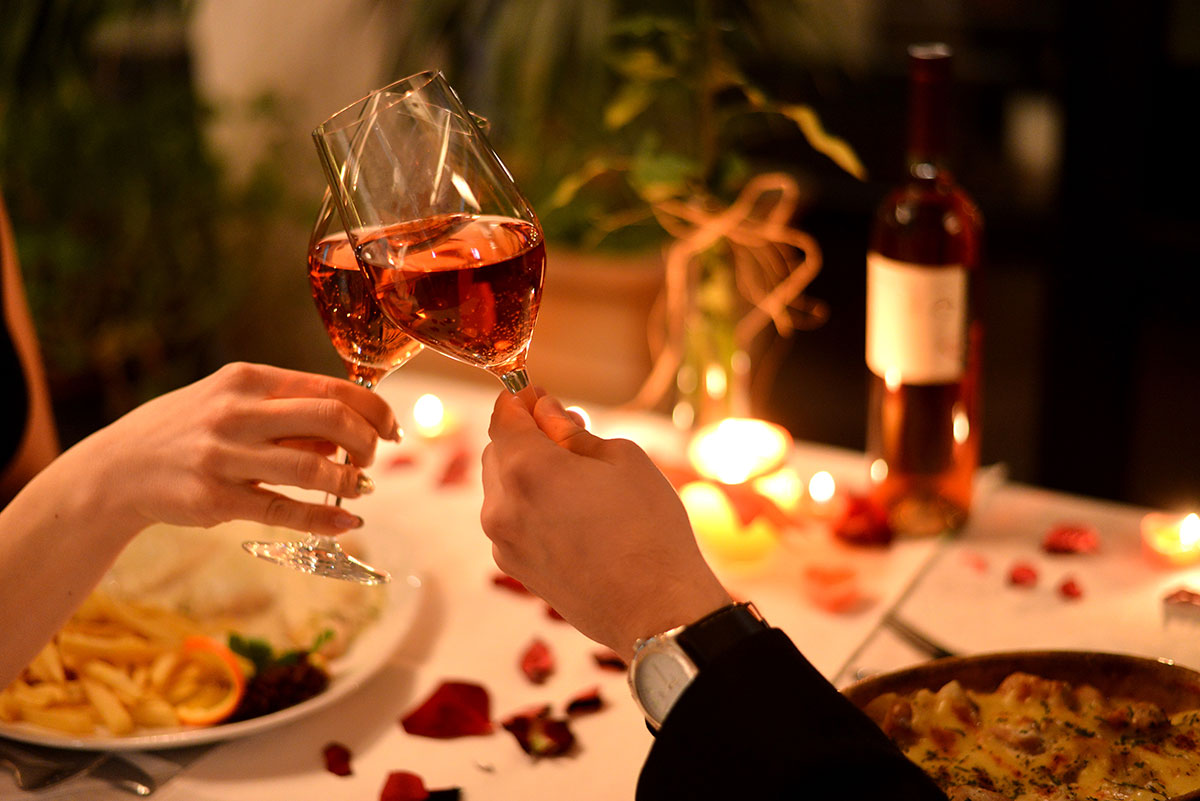 couple clinking glasses of wine on a date night dinner