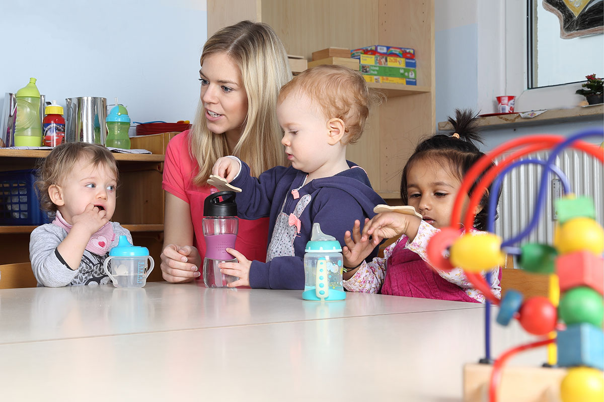 three children at daycare with their childcare provider