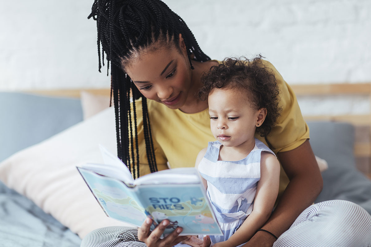 childcare provider reading to young girl