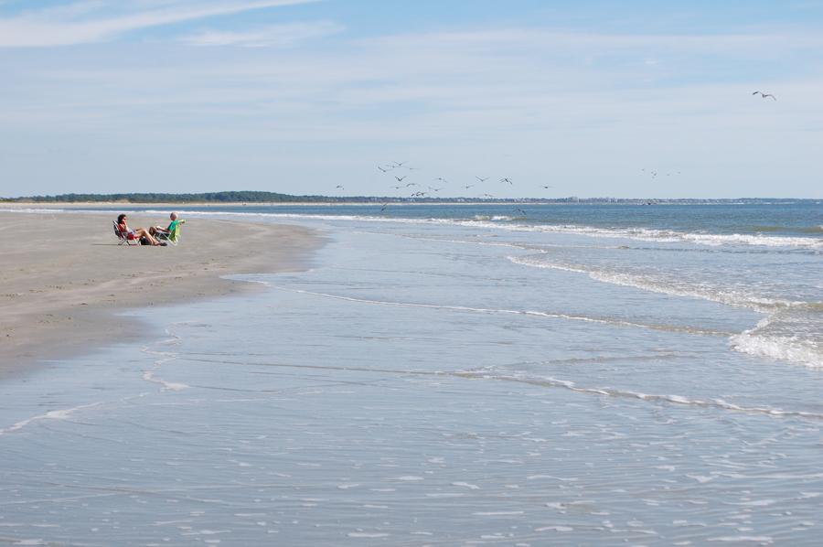 couple enjoys quiet beach with blue skies