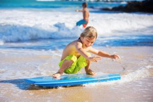 young boy standing on a boogie board