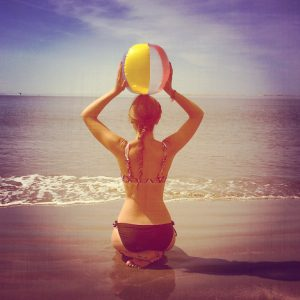 woman holding beach ball on the beach