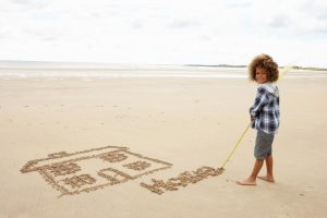 boy drawing a house in the sand