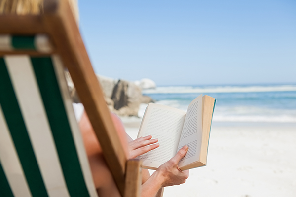 woman reading books for summer reading while sitting in chair