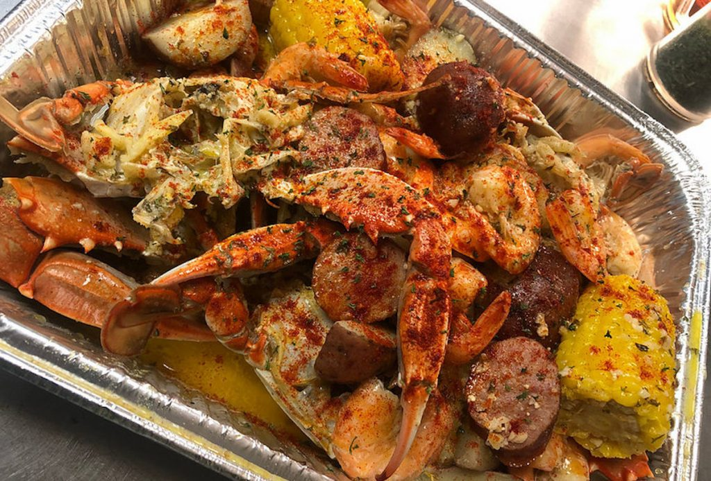 Sausage, seafood, corn, and potatoes served on a platter