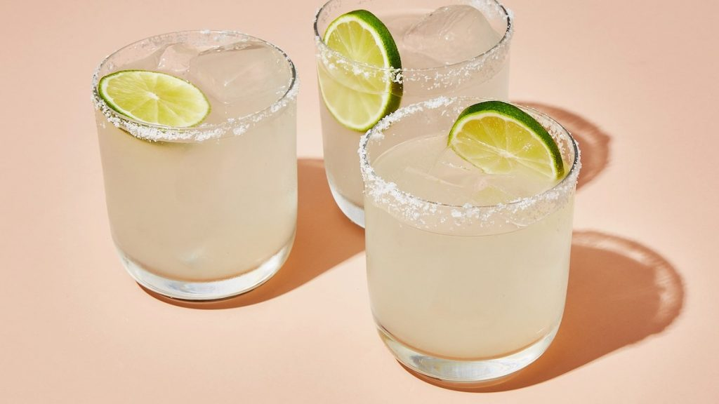Image of Mojitos with limes in them and sugar around the rim