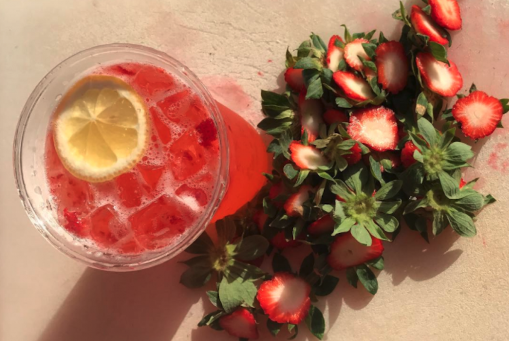 Strawberry lemonade in a container with a lemon slice and ice, chopped up strawberries lay in an adjacent pile