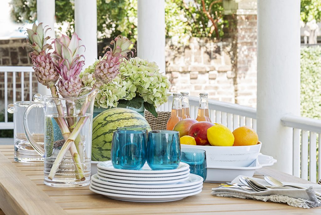Beautiful outdoor dining setting with blue glasses, white plates, florals, a fruit bowl, a watermelon, utensils, and some bottled drinks set on the table
