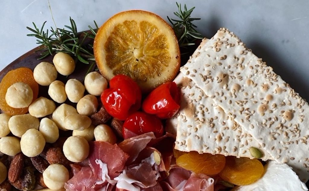 Crackers, nuts, peppers, herbs, and meat are seen on a charcuterie board