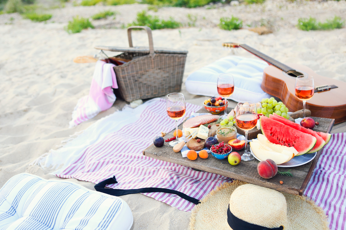 Beach picnic with wine, fruit, and cheese on a blanket. On the same blanket lies a hat, cushion, basket, and a guitar.